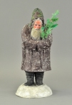 "Very large composition Belsnickle in dark purple robe with holly leaves on top of hood, beautiful blue glass eyes and glass icicle beard, holds seven branch feather tree, he stands on mica covered snow mound. 19"" h. From Auction News."